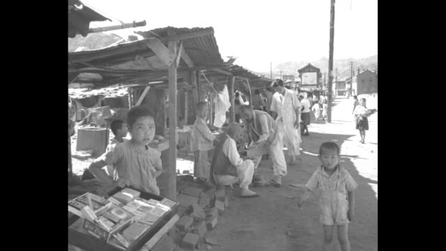 little boys playing in front of makeshift shelter in front of bombed out building / vendors in makeshift stalls made of tarps and scraps young girls... - korean war stock videos & royalty-free footage