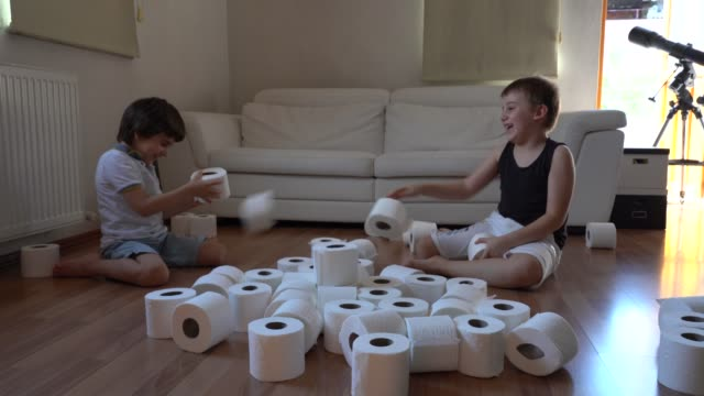 little boys plays with toilet papers when she is bored at home during pandemic - tessuto umano video stock e b–roll