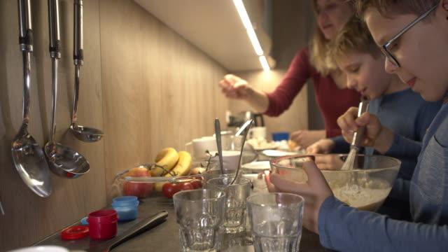 vídeos y material grabado en eventos de stock de niños pequeños preparando tortilla con la madre - dolly shot
