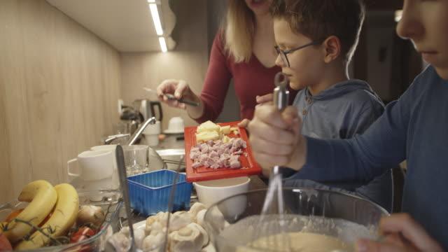 kleine jungen bereiten omelett mit mutter - hart arbeiten stock-videos und b-roll-filmmaterial