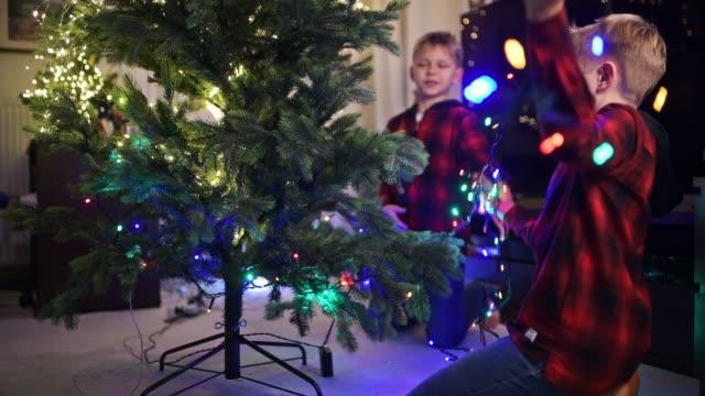 little boys putting christmas lights on christmas tree - imgorthand stock videos & royalty-free footage