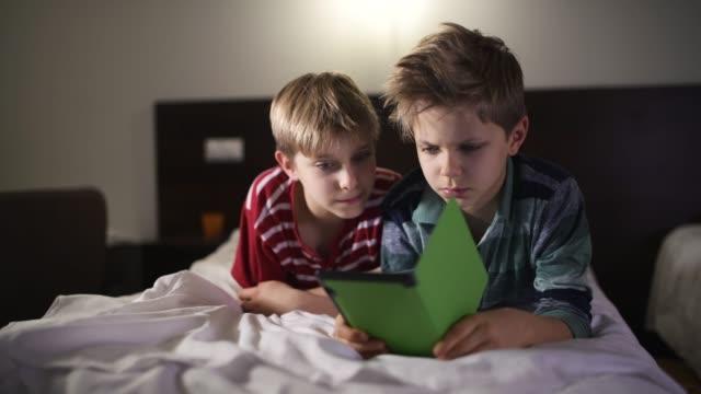 little boys reading book using e-reader - e book stock videos & royalty-free footage
