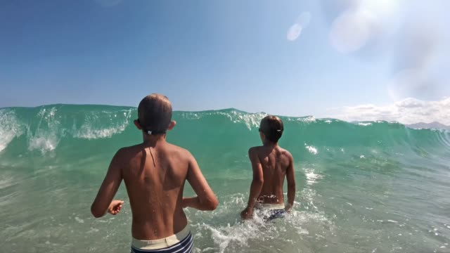 little boys splashed by sea wave - beach holiday stock videos & royalty-free footage