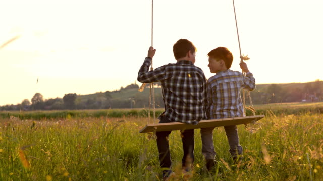 slo mo little boys swinging on the swing - rope swing stock videos & royalty-free footage