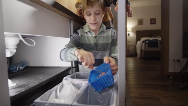 kleine jungen werfen organische abfälle in abgetrennte mülltonne - auseinander stock-videos und b-roll-filmmaterial