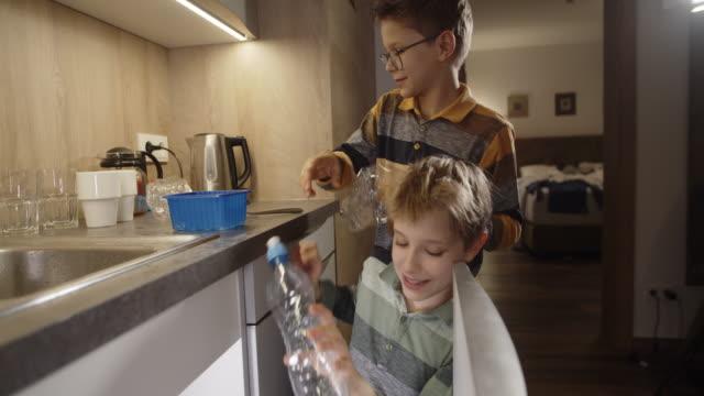 vídeos de stock e filmes b-roll de little boys throwing plastic bottles to separated garbage bin - reciclagem