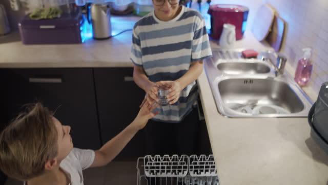 små pojkar lossning diskmaskinen - ansvar bildbanksvideor och videomaterial från bakom kulisserna