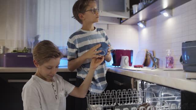 vidéos et rushes de petits garçons déchargeant le lave-vaisselle - lave vaisselle