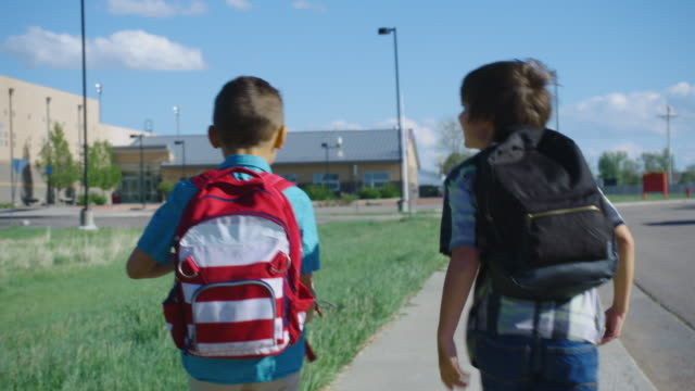 vídeos de stock e filmes b-roll de little boys walk to school - criança de escola primária