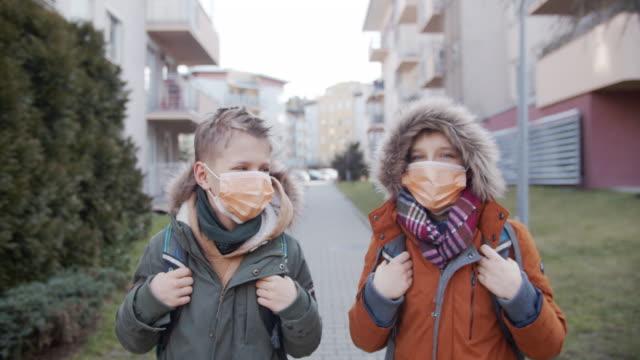 små pojkar bär gasmasker går i skolan - kirurgmask bildbanksvideor och videomaterial från bakom kulisserna