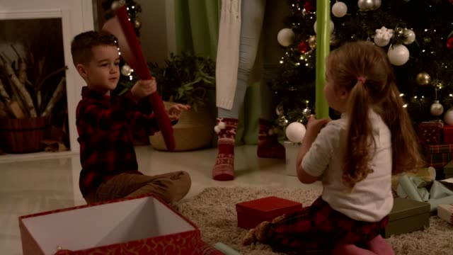 little brother and sister playing sword fight with wrapping papers - christmas wrapping paper stock videos & royalty-free footage