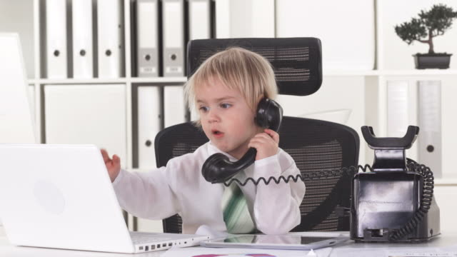hd: little business boy with multitasking skills - hot desking stock videos & royalty-free footage