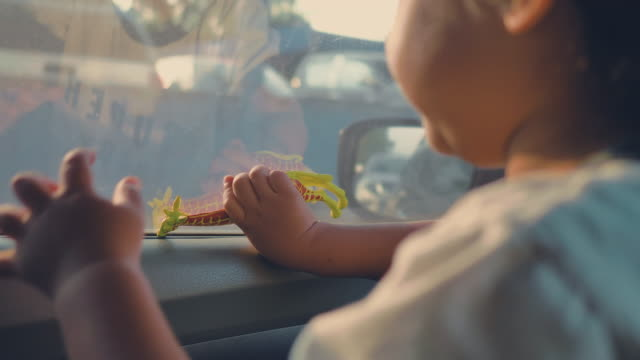 little cheerful boy sits playing toy in car. - soltanto un neonato maschio video stock e b–roll