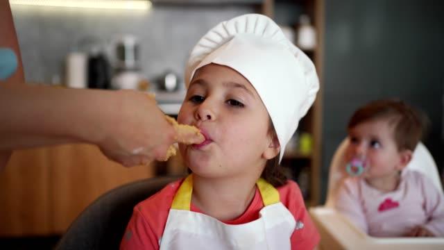 vídeos y material grabado en eventos de stock de pequeño chef aprobando la mezcla de su madre para un pastel - gesticular