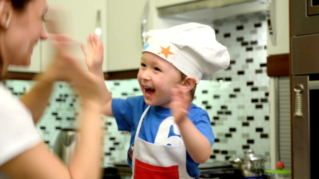 little chef cooking with his mother at home - high five stock videos & royalty-free footage