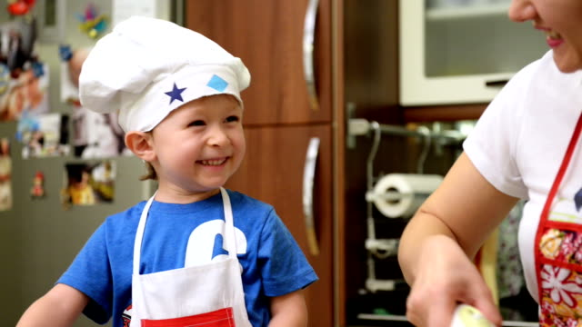 little chef cooking with his mother at home - chef's hat stock videos & royalty-free footage