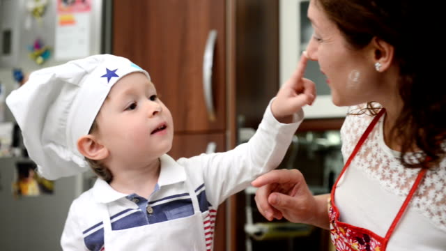 Little chef cooking with his mother at home
