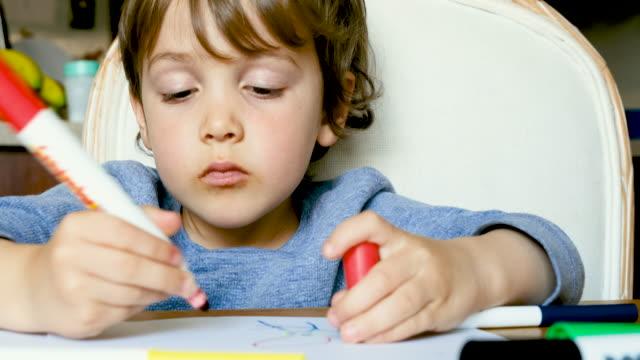 vídeos de stock e filmes b-roll de little child boy doing his homework at his home backyard - caneta de feltro