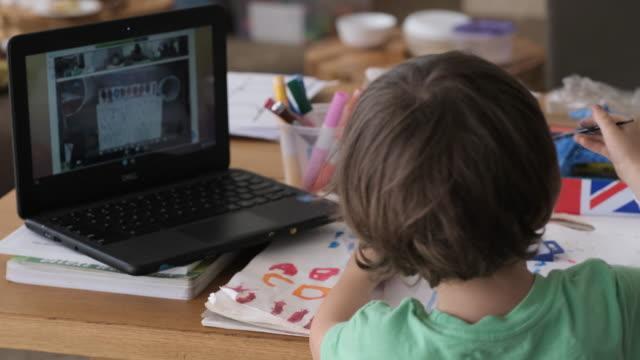 kleiner junge, der eine vorschulklasse mit fernunterricht verfolgt - stift stock-videos und b-roll-filmmaterial
