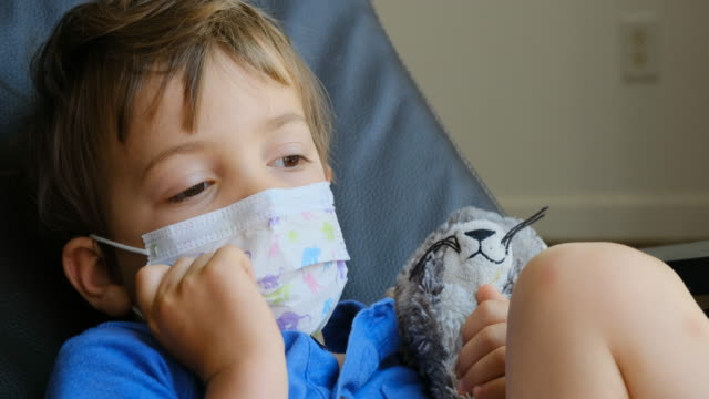 little child boy looking away wearing a surgical mask - children only stock videos & royalty-free footage