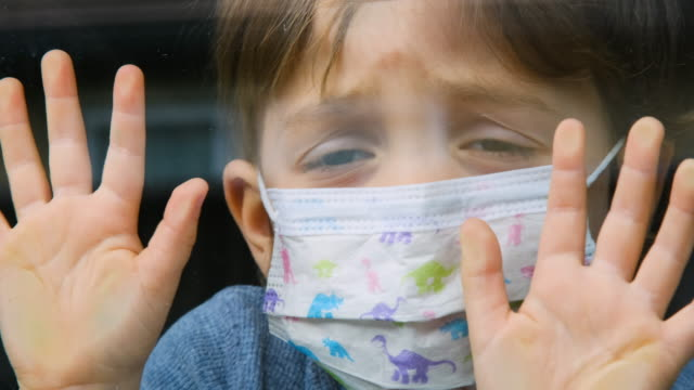little child boy looking through a window using a surgical mask - loneliness stock videos & royalty-free footage