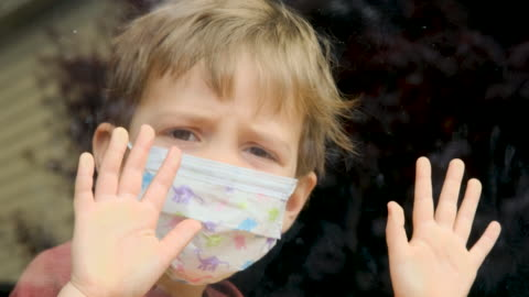 little child boy looking through a window using a surgical mask - trapped stock videos & royalty-free footage