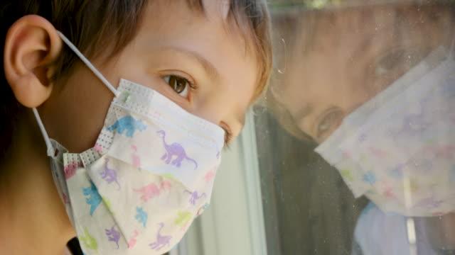 bambino che guarda attraverso una finestra usando una maschera chirurgica - interno di casa video stock e b–roll