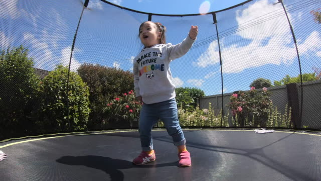 little child enjoys jumping on trampoline - toddler stock videos & royalty-free footage