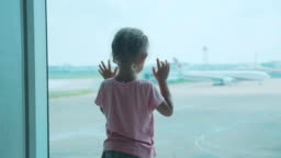 Little child girl looks out of window on airplane, rear wiew.