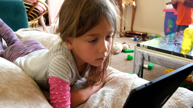 little child girl using an electronic tablet - reclining stock videos & royalty-free footage