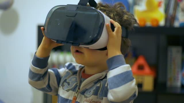 vídeos y material grabado en eventos de stock de little child is using vr glass in his bedroom - nativo digital