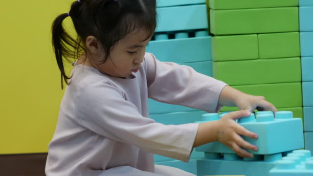Little child playing toy in playground room