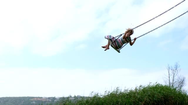vídeos y material grabado en eventos de stock de niño pequeño columpia alto en un columpio de madera - columpio