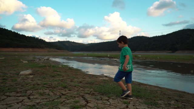 little child walking near plastic wastes on dry lake bed, cracked earth - lake bed stock videos & royalty-free footage
