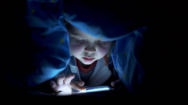 Little child, with blue eyes, watching a digital tablet under the bed sheets