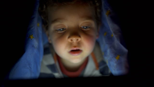 vídeos de stock e filmes b-roll de little child, with blue eyes, watching a digital tablet under the bed sheets - lençol roupa de cama