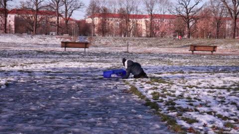 little child (3) with winter cap getting off a sled. - 40 sekunder eller längre bildbanksvideor och videomaterial från bakom kulisserna