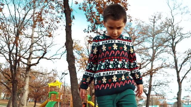 vídeos de stock, filmes e b-roll de garotinho fofo irritado com suéter de natal feio está jogando em folhas caídas em dezembro - suéter