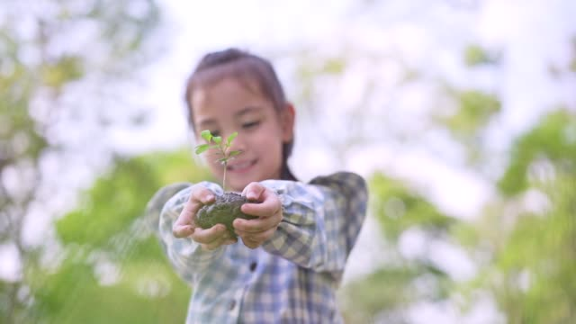 little cute asian girl give small plant to mother,save the earth concept.