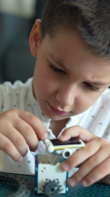 little cute boy builds solar powered robot - vertical 4k video - 6 7 years stock videos & royalty-free footage