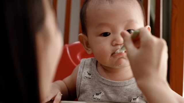 little cute boy happily eating baby porridge - wishing well stock videos & royalty-free footage