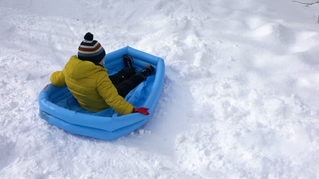 little cute boy slide on snow with inflatable pool - audio available stock videos & royalty-free footage