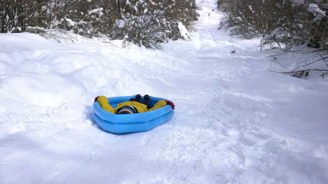 little cute boy slide on snow with inflatable pool - 6 7 years stock videos & royalty-free footage