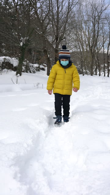 little cute boy walking on snow in forest - 4k vertical video - 6 7 years stock videos & royalty-free footage