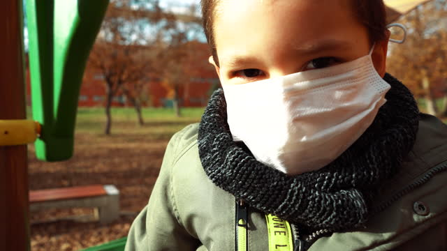 little cute boy with surgical mask is playing in child park on fallen leaves in autumn - 4 5 years stock videos & royalty-free footage