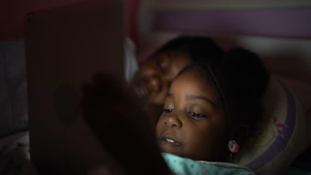 vídeos de stock, filmes e b-roll de menina bonitinha e sua mãe usando tablet digital à noite - afro