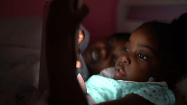 little cute girl and her mother using digital tablet at night - using digital tablet stock videos & royalty-free footage