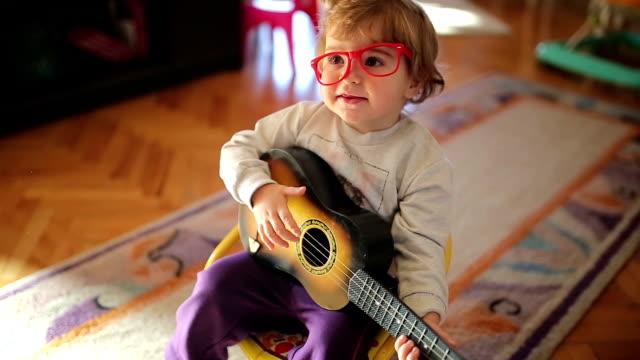 vídeos y material grabado en eventos de stock de poco lindo chica canta y tocando guitarra de juguete - cantar