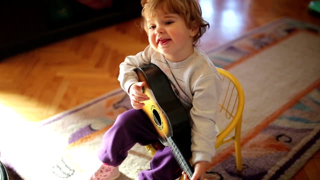 little cute girl playing toy guitar and singing - baby girls stock videos & royalty-free footage