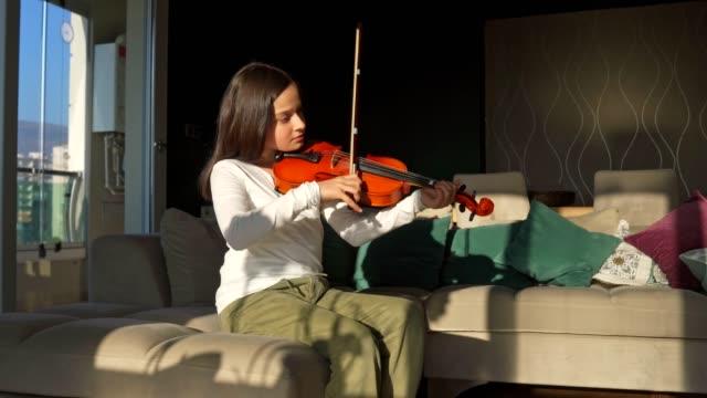 vídeos de stock e filmes b-roll de little cute girl playing violin at home - violino